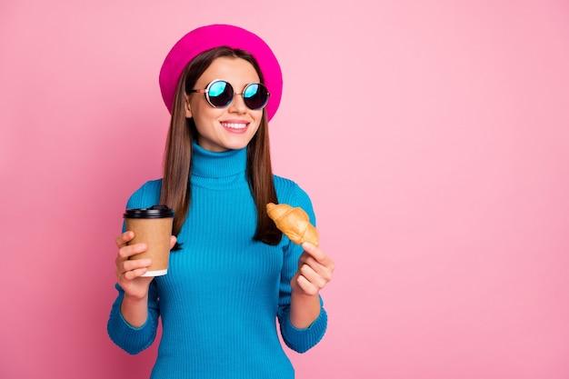 Portret van positieve meisjereisreis genieten van café rust houden afhalen mok latte drank heerlijke croissant dragen blauwe retro zonnebril hoofddeksels. Premium Foto