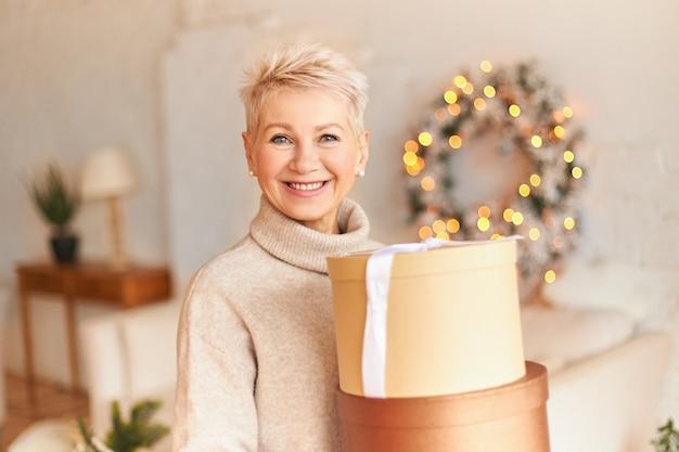 Portret van positieve volwassen vrouw in trui met stralende gelukkige glimlach poseren in gezellige woonkamer met feestelijke decoraties, doos met cadeautjes van zoon te houden. vrolijk kerstfeest Gratis Foto