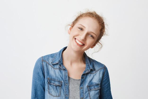 Portret van positieve vriendelijke europese roodharige meisje recht hoofd kantelen en breed lachend, kijkend naar de camera met zuivere blauwe ogen Gratis Foto