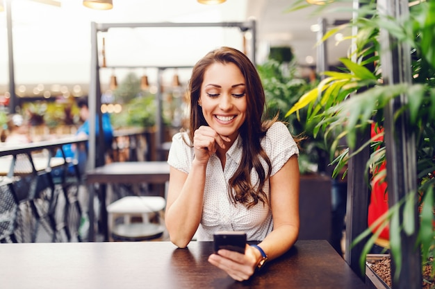 Portret van prachtige kaukasische brunette in shirt met behulp van slimme telefoon en zittend aan de bar. Premium Foto