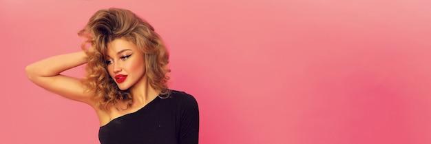 Portret van prachtige mooie vrouw met grote rode lippen. moderne lichte make-up op haar mooie gezicht, krullend kapsel. slank sexy lichaam, gekleed in zwarte top met open schouder. Gratis Foto