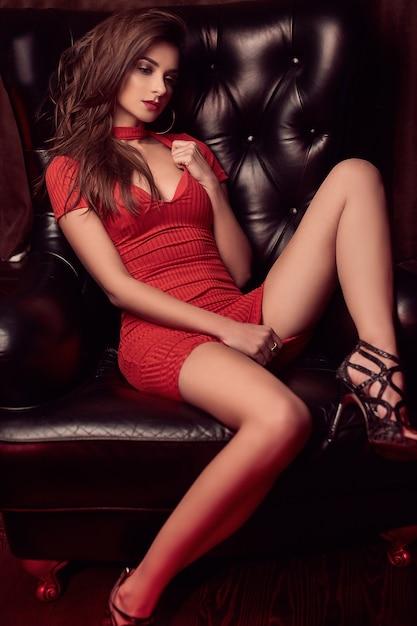 Portret van prachtige schoonheid jonge brunette vrouw in rode jurk zittend in een lederen stoel Gratis Foto