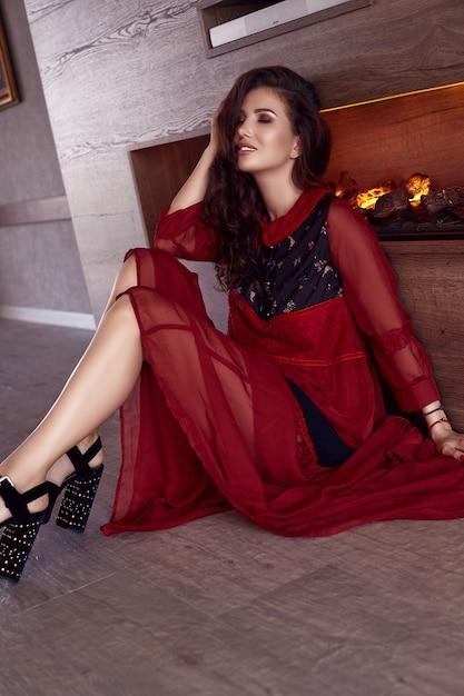 Portret van prachtige sensuele brunette model in mode rode jurk poseren bij de open haard Gratis Foto