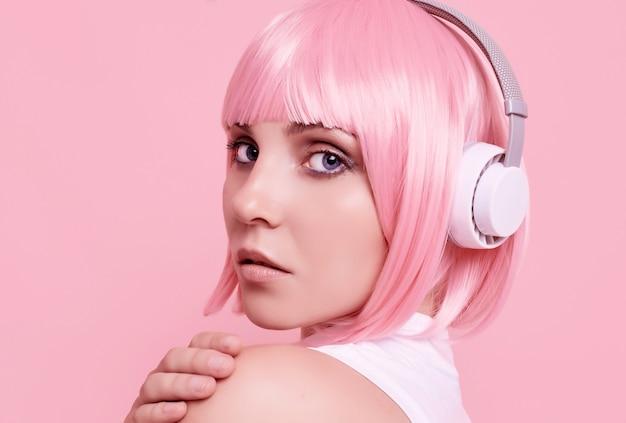 Portret van prachtige vrouw met roze haren geniet van de muziek in de koptelefoon Gratis Foto