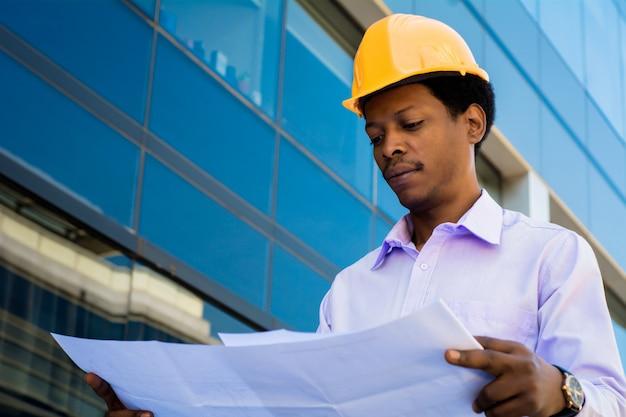 Portret van professionele architect die in helm blauwdrukken buiten modern gebouw bekijkt. ingenieur en architect concept. Gratis Foto
