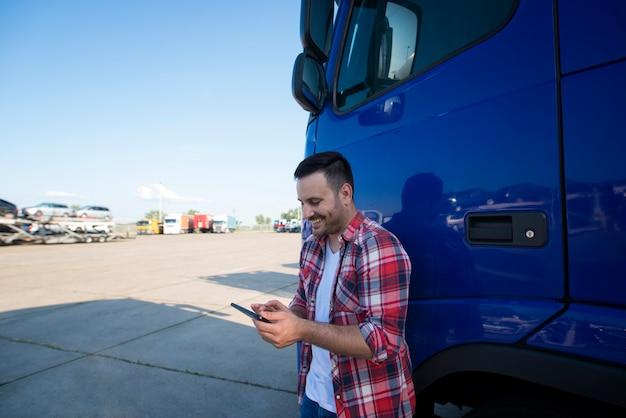 Portret van professionele vrachtwagenchauffeur van middelbare leeftijd die zich door zijn vrachtwagen bij vrachtwagenstop bevindt die tabletcomputer gebruikt Gratis Foto