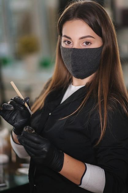 Portret van professionele vrouwelijke wenkbrauwmeester in zwart gewaad met zwarte handschoenen en zwart beschermend masker gebruik borstel en henna voor wenkbrauwen Premium Foto