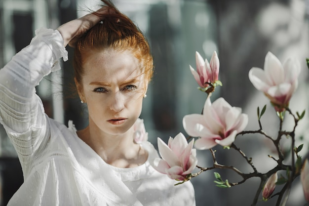 Portret van redhead vrouw dichtbij een magnoliatakje Gratis Foto