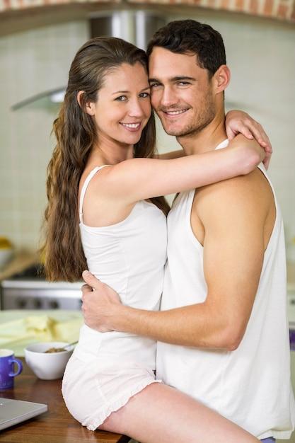 Portret van romantische jong koppel knuffelen op keuken aanrecht Premium Foto