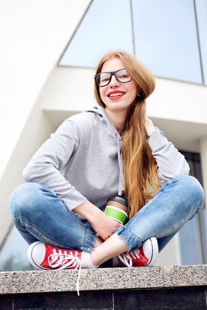 Portret van roodharigemeisje gekleed in hoody, jeans, rode tennisschoenen en glazen Premium Foto
