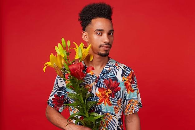 Portret van rustige jonge afro-amerikaanse man, draagt in hawaiiaans shirt, kijkt naar de camera, houdt gele en rode bloemen, staat op rode achtergrond. Gratis Foto