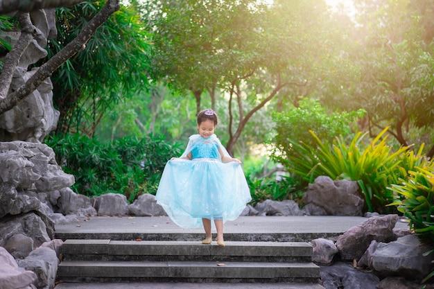 Portret van schattig glimlachend meisje in prinses kostuum lopen de trap af in het park Premium Foto