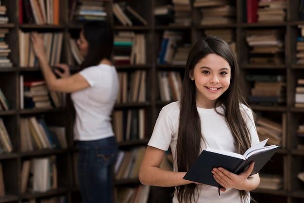 Portret van schattig jong meisje met een boek Gratis Foto