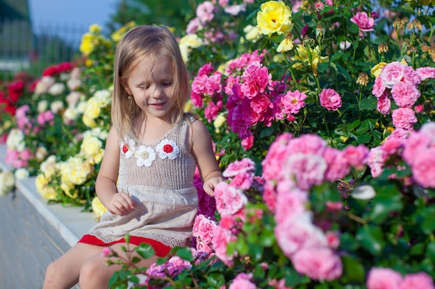 Portret van schattig klein meisje in de buurt van de bloemen in de tuin van haar huis Premium Foto