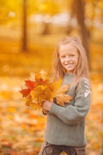 Portret van schattig klein meisje met gele bladeren boeket in de herfst Premium Foto