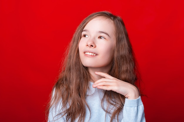 Portret van schattig klein meisje wegkijken over rode muur Premium Foto