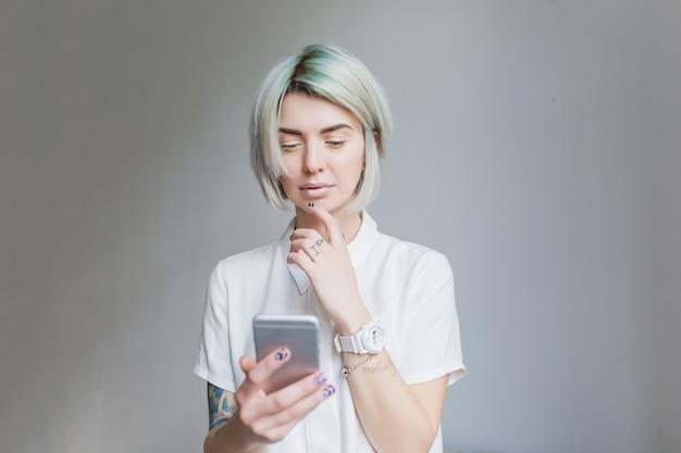 Portret van schattig meisje met grijze korte haarstijl staande op een grijze achtergrond. ze draagt een witte jurk en lichte make-up, houdt de telefoon vast. Gratis Foto