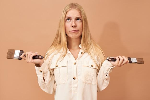 Portret van schattige besluiteloze jonge vrouw met sluik blond haar poseren geïsoleerd met verfborstels, opzoeken met peinzende gezichtsuitdrukking, twijfelachtig Gratis Foto