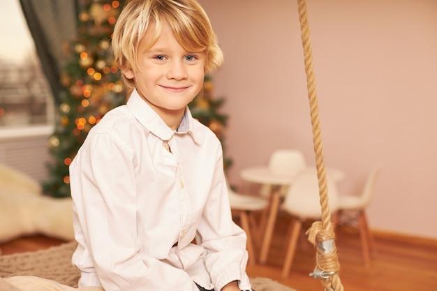 Portret van schattige europese jongen dragen wit overhemd genieten van feestelijke stemming, anticiperen op kerstavond, zittend in de woonkamer met versierde new year's boom, gelukkig lachend Gratis Foto
