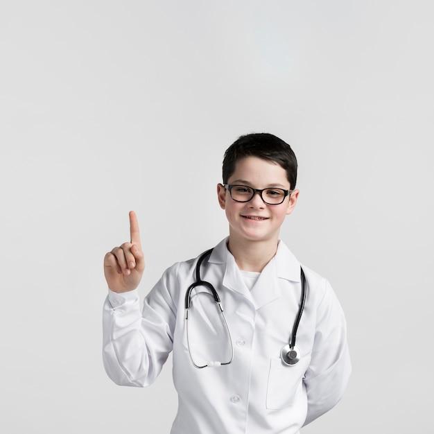 Portret van schattige jonge jongen die omhoog wijst Gratis Foto