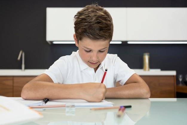Portret van schattige jonge jongen huiswerk Gratis Foto