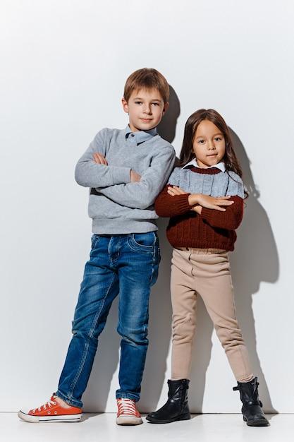 Portret van schattige kleine jongen en meisje in stijlvolle jeans kleding camera kijken in de studio Gratis Foto