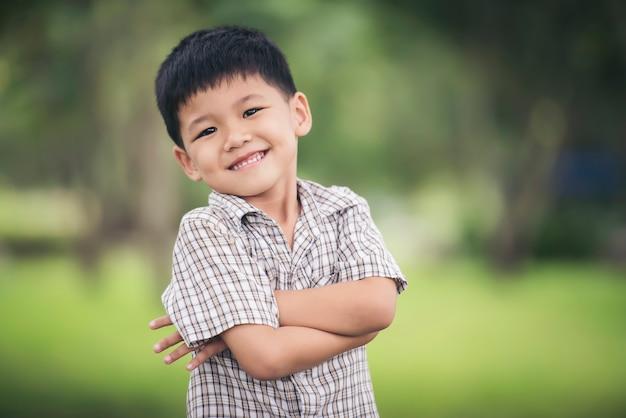 Portret van schattige kleine jongen permanent met armen gevouwen en kijken naar de camera Gratis Foto