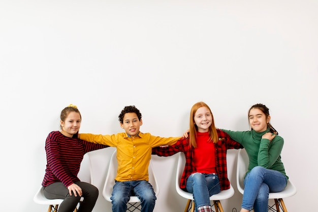 Portret van schattige kleine kinderen in spijkerbroek zittend in stoelen tegen de witte muur Premium Foto