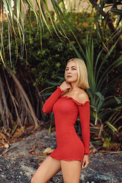 Portret van schattige, knappe blonde dame in korte rode jurk met sexy figuur, Premium Foto