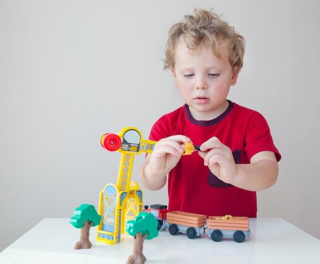 Portret van schattige peuter jongen zittend aan tafel spelen met een houten constructie auto thuis. klein kind met speelgoedauto Premium Foto