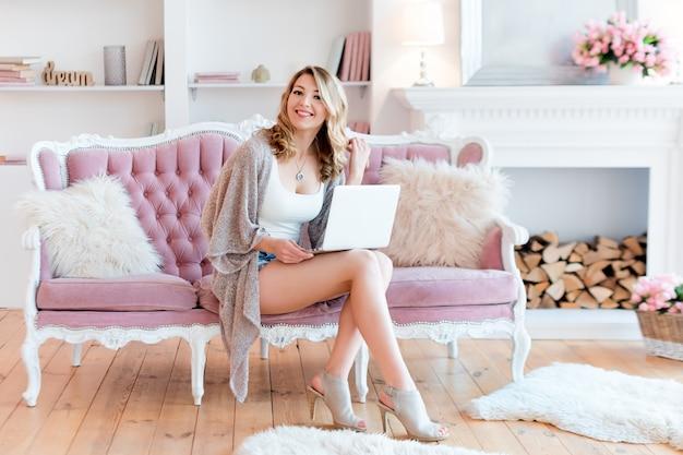 Portret van schitterende blondevrouw met laptop die thuis werken. Premium Foto
