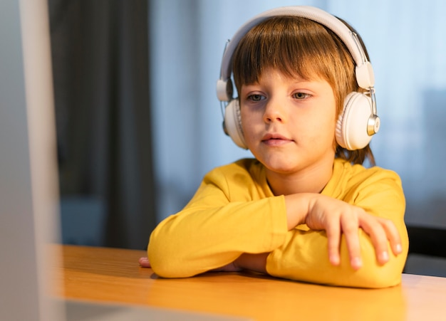Portret van schooljongen in geel overhemd die virtuele lessen nemen Gratis Foto
