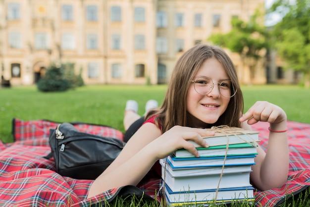 Portret van schoolmeisje die op deken met boeken leggen Gratis Foto