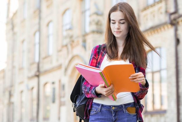 Portret van schoolmeisje met boek in stad Gratis Foto