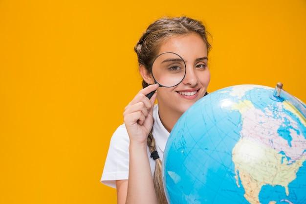 Portret van schoolmeisje met een wereldbol Gratis Foto