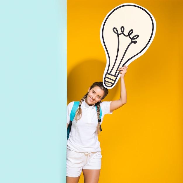 Portret van schoolmeisje met grote gloeilamp Gratis Foto