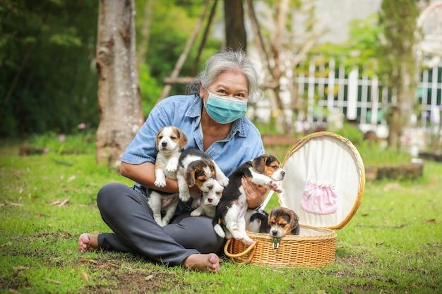 Portret van senior azië vrouw met beschermend masker en met haar puppy hondje spelen in het park. Premium Foto