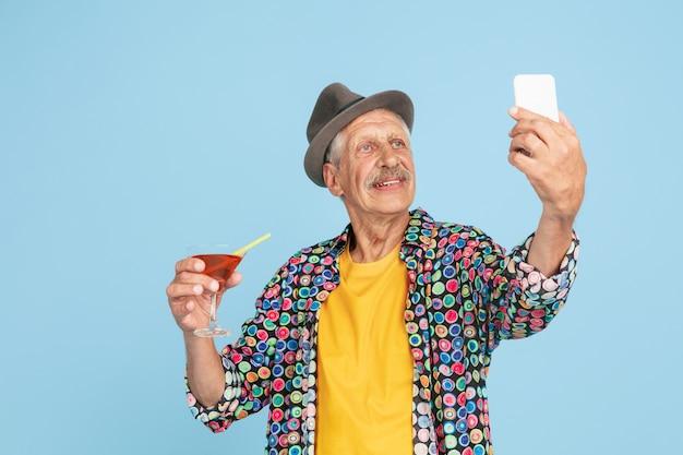 Portret van senior hipster man met behulp van apparaten, gadgets geïsoleerd op lichte studio achtergrond. tech en vreugdevolle ouderen levensstijl concept. Gratis Foto
