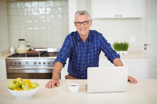 Portret van senior man met laptop in de keuken Premium Foto