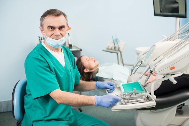 Portret van senior mannelijke tandarts met tandheelkundige instrumenten in de tandheelkundige kantoor Premium Foto