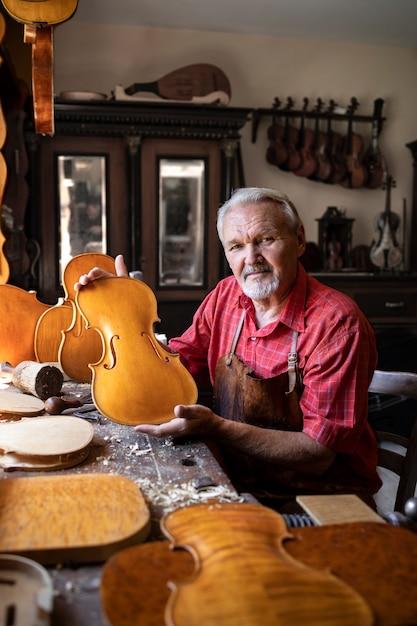 Portret van senior timmerman in zijn ouderwetse werkplaats violen muziekinstrument maken voor kunstacademie Gratis Foto