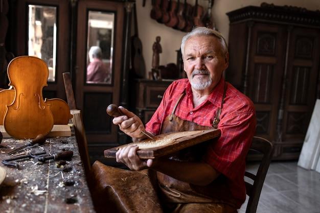 Portret van senior timmerman met tools en hout in zijn ouderwetse werkplaats Gratis Foto