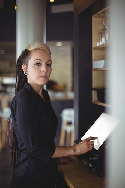 Portret van serveerster die kasregister gebruiken bij teller Gratis Foto