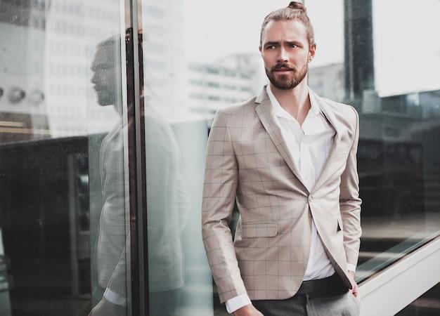 Portret van sexy knappe man gekleed in elegant beige geruit pak Gratis Foto