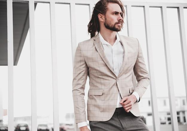 Portret van sexy knappe mode mannelijk model man gekleed in elegant beige geruit pak Gratis Foto