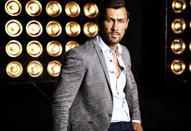 Portret van sexy knappe mode mannelijk model man gekleed in elegant pak op studio lichten achtergrond Gratis Foto