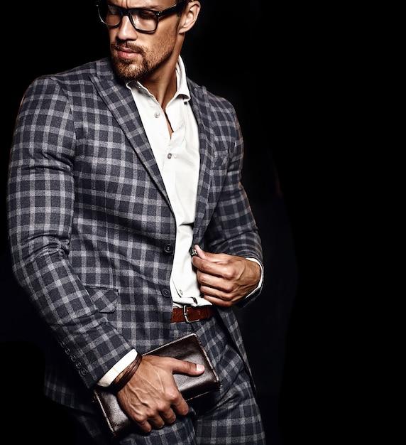 Portret van sexy knappe mode mannelijk model man gekleed in elegant pak op zwarte achtergrond Gratis Foto