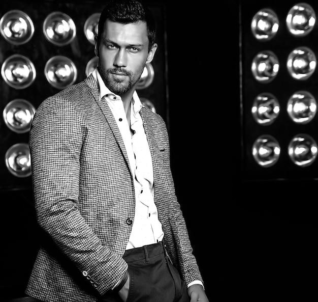 Portret van sexy knappe mode mannelijk model man gekleed in elegant pak op zwarte studio lichten achtergrond Gratis Foto