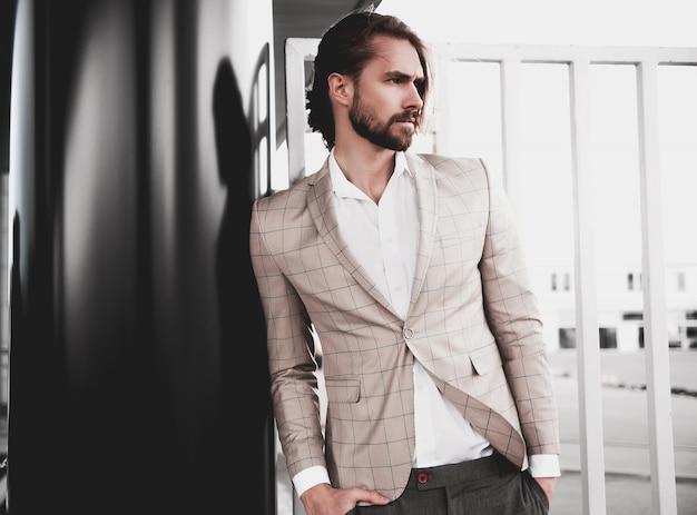 Portret van sexy knappe mode mannelijk model man gekleed in elegante beige geruit pak die zich voordeed op de straat achtergrond Gratis Foto