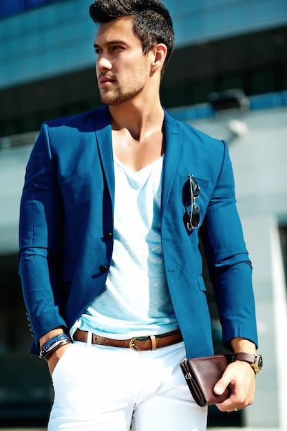 Portret van sexy knappe mode mannelijk model man gekleed in elegante pak die zich voordeed op de straat achtergrond Gratis Foto